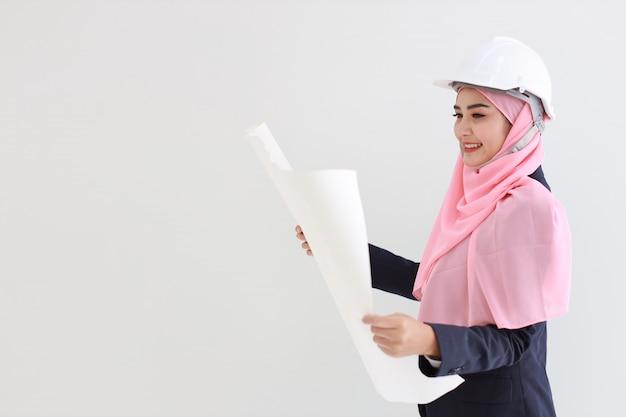 Slimme moslim jonge aziatische vrouw die blauw kostuum dragen die zekere holdingsblauwdruk glimlachen