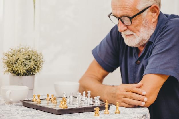 Slimme ouderling die thuis schaakbordspel speelt om het geheugen van de hersenen te trainen en blij lachend selectieve aandacht bij het schaakstuk denkt.