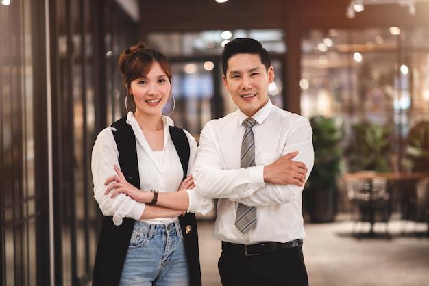Slimme paar mkb-bedrijfseigenaar die zich met gekruiste armen zelfverzekerd in nieuw bedrijf bevindt