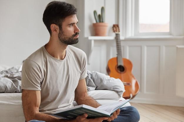 Slimme professionele bebaarde man thuis poseren tijdens het werken