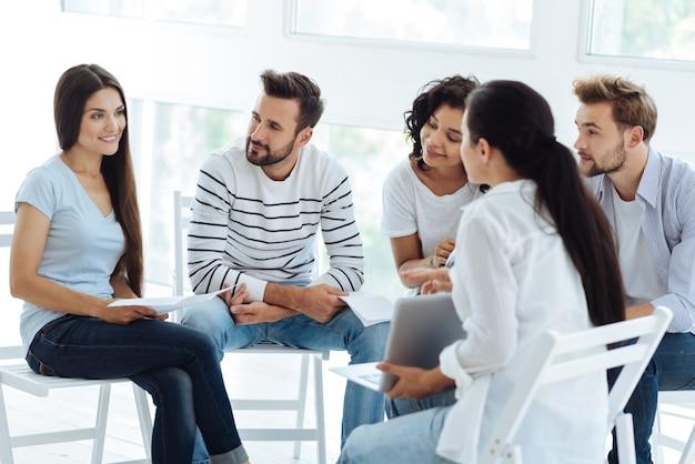 Slimme professionele ervaren psycholoog die een laptop vasthoudt en deze aan haar patiënten laat zien terwijl ze technologie in haar werk gebruikt