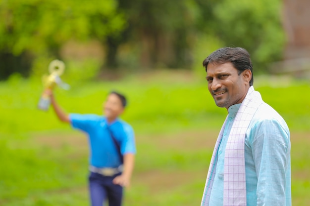 Slimme schooljongen die een winnende trofee vasthoudt en bij zijn vader staat