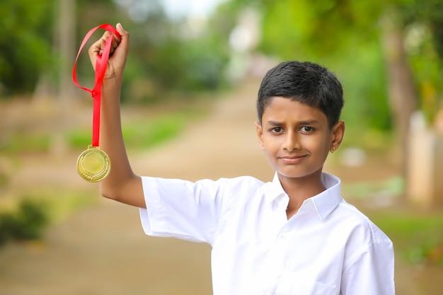 Slimme schooljongen die zijn gouden medaille ophaalt als winnaar in de schoolcompetitie.