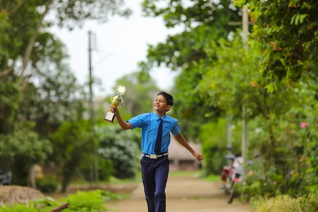 Slimme schooljongen die zijn trofee opheft als winnaar in de schoolcompetitie.