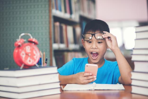 Slimme schooljongen huiswerk met telefoon