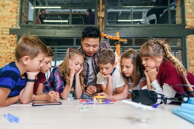 Slimme schoolkinderen met aziatische mannelijke leraar onderzoeken elektronische constructor met draaiende ventilator en lamp. creatieve leerlingen met wetenschapper die werken aan het tech-project op school.