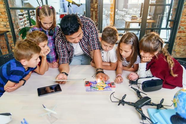 Slimme schoolkinderen met aziatische mannelijke leraar onderzoeken elektronische constructor met draaiende ventilator en lamp