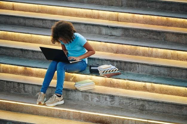 Slimme schoolmeisje zittend op trappen met veel boeken rond en bezig met laptop