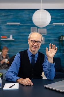 Slimme senior zakenman die op laptop werkt met een stropdas en een bril. oudere man ondernemer in thuiswerkplek met behulp van draagbare computer zittend aan een bureau terwijl de vrouw de afstandsbediening van de tv vasthoudt.