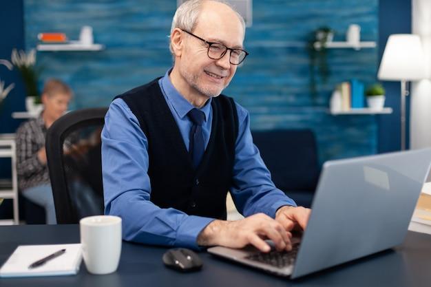 Slimme senior zakenman die op laptop werkt met een stropdas en een bril