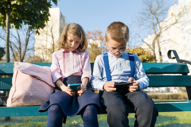 Slimme serieuze kinderen jongen en meisje zijn op zoek naar smartphones