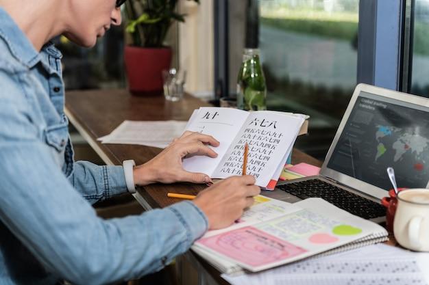 Slimme student. aangename jongeman die zijn huiswerk doet terwijl hij in het boek kijkt