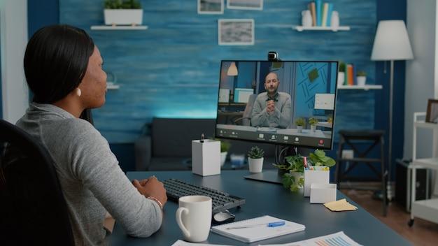 Slimme student die werkt aan een marketingdeadlineproject dat academische ideeën bespreekt met een ondernemer tijdens een online videogesprek-teleconferentievergadering