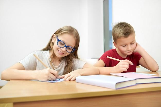 Slimme studenten die in klaslokaal zitten en test doen op school