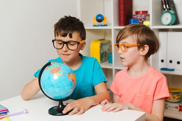 Slimme studenten kijken naar globe. schooljongens die aardrijkskunde studeren. kinderen die samen huiswerk maken.