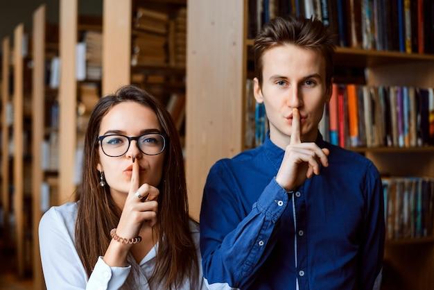 Slimme studentennerds in de bibliotheek die in de camera kijken en stilte gebaar maken