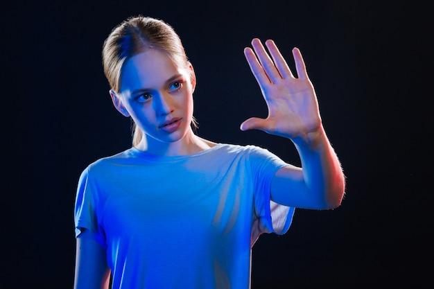 Slimme technologie. leuke jonge vrouw die naar haar hand kijkt terwijl ze het sensorische scherm aanraakt