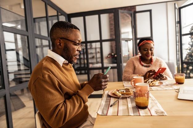 Slimme technologieën. aardige serieuze man die zijn smartphone gebruikt terwijl hij aan de tafel in de eetkamer zit
