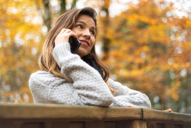 Slimme telefoon herfst vrouw praten op mobiele telefoon in de herfst. herfst meisje met smartphone gesprek in zon flare gebladerte. portret van kaukasische jonge vrouw in bos in herfstkleuren.