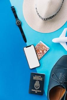 Slimme telefoon; kaart; paspoort; speelgoedvliegtuig; schoenen; polshorloge en hoed op dubbele achtergrond