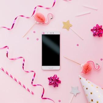Slimme telefoon; streamers; rietjes; feesthoed; flamingo's en sterretje op roze achtergrond