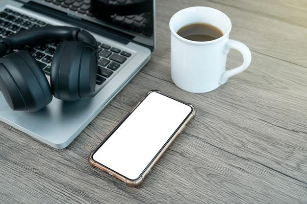 Slimme telefoon wit mock-up scherm. werkplek bureau. plat lag werkruimte met laptop kopje koffie op houten achtergrond.