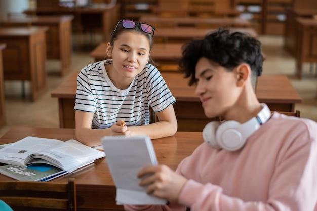 Slimme tienermeisje wijzend op notities in kladblok van haar klasgenoot tijdens bespreking van punten van seminar in universiteitsbibliotheek
