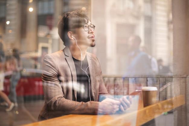 Slimme uitziende man zit in een café, luisteren naar iets op zijn telefoon