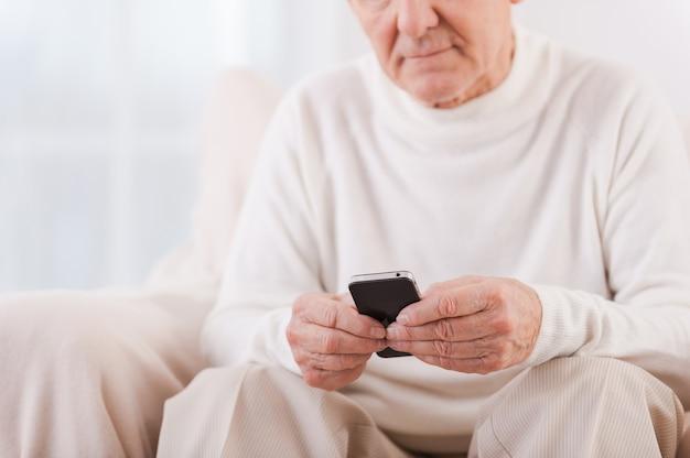 Slimme volwassenheid. close-up van senior man die mobiele telefoon vasthoudt terwijl hij in de stoel zit