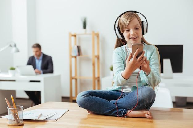 Slimme, vrolijke meid die haar telefoon gebruikt om het juiste nummer te kiezen terwijl ze een koptelefoon draagt