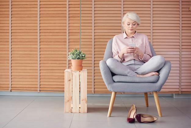 Slimme vrouw die in een fauteuil zit en een sms leest