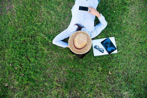 Slimme vrouw die op het gras legt