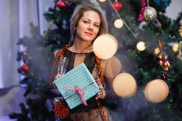 Slimme vrouw verheugt zich met een geschenkdoos in de buurt van een kerstboom. een vrouw lacht, glimlacht, poseert. speciale vintage ruis- en graanfilter, wazige lichten.