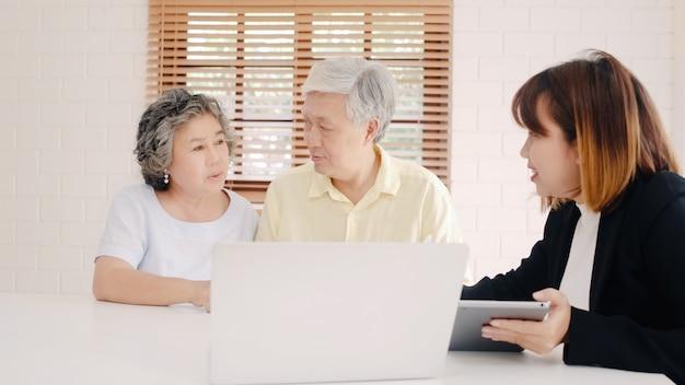 Slimme vrouwelijke agent azië biedt ziektekostenverzekering voor oudere koppels door document, tablet en laptop.