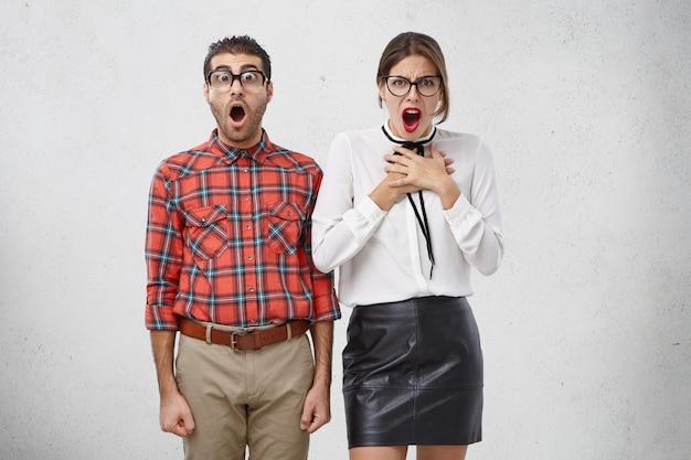 Slimme vrouwelijke en mannelijke studenten kijken geschokt en verontwaardigd naar de camera, vraag professor waarom ze al het werk alleen zouden moeten doen