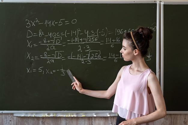 Slimme vrouwelijke student die op een bord schrijft die algebra-wiskundige formules voltooit, onderwijsconcept
