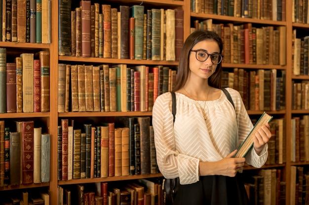 Slimme vrouwelijke student met boek in de bibliotheek