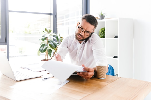 Slimme zakenman 30s in wit overhemd praten op mobiele telefoon tijdens het onderzoek van informatie uit papieren documenten in kantoor