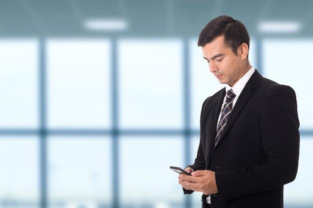 Slimme zakenman die slimme telefoon gebruikt voor werk met team sociale mediagroep.