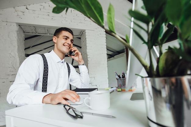Slimme zakenman zit en gebruikt de computer voor werk op kantoor