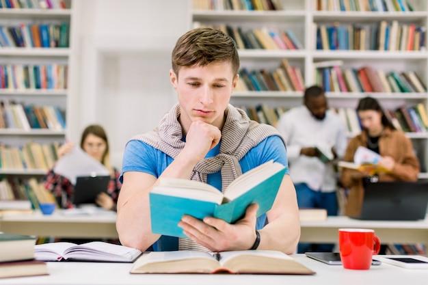 Slimme zekere jonge kaukasische mens die in bibliotheek voor test of examen bestudeert, zit hij bij bureau en leest een boek