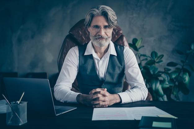 Slimme zelfverzekerde oude man ondernemer zitten tafel in moderne kantoren