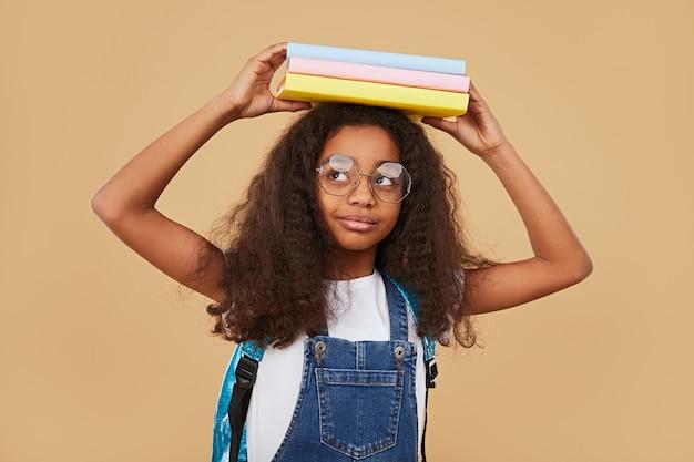 Slimme zwarte schoolmeisje met schoolboeken