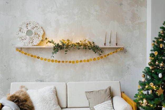 Slinger van gedroogde sinaasappels of citroenen op de plank boven de bank en de kerstboom
