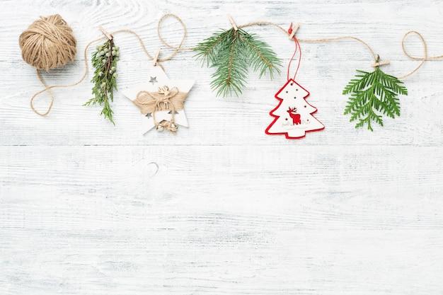 Slinger van kerstmisdecoratie en naaldboomtakken op witte achtergrond