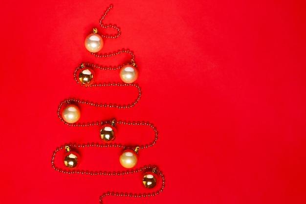 Slinger van kralen in de vorm van een kerstboom met gouden ballen