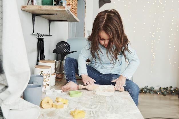 Slingers en vakantiedecoratie op de achtergrond. foto van mooi meisje dat op de keukentafel zit en met bloem speelt