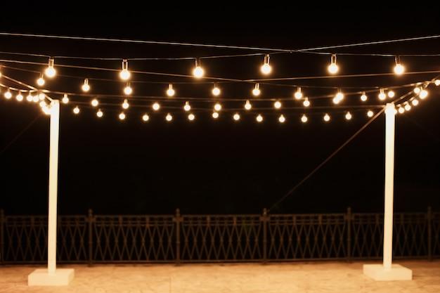 Slingers van lampen op een houten standaard op straat. een bruiloftsbanket.