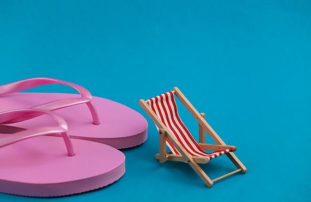 Slippers en mini strand ligstoel op blauw. symbool van strandvakanties, resort.
