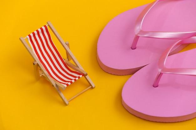 Slippers en mini strand ligstoel op geel. symbool van strandvakanties, resort.